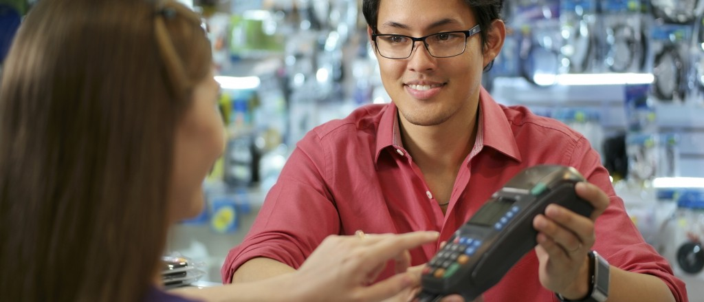 Customer Paying With Credit Card In Chinese Computer Shop