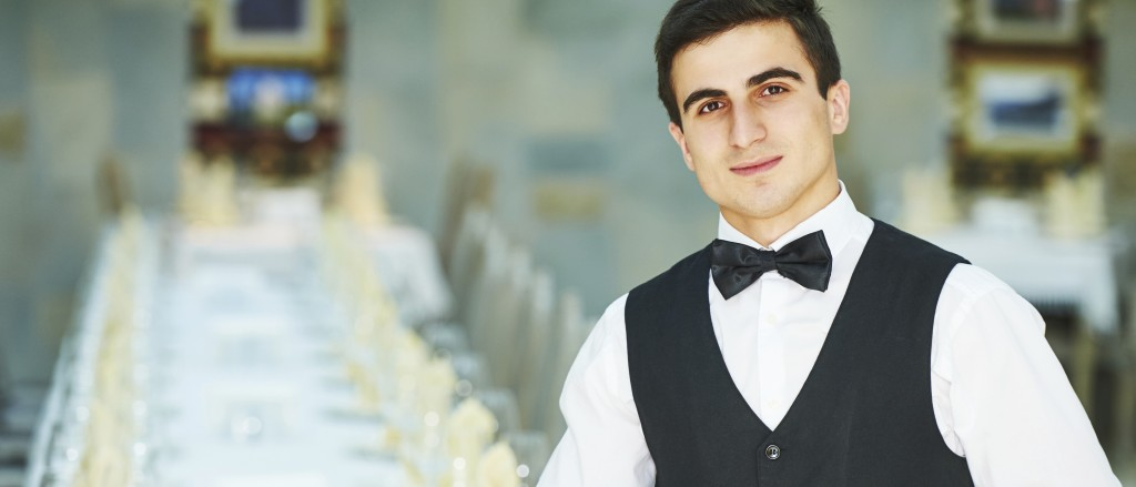 young waiter at service in restaurant