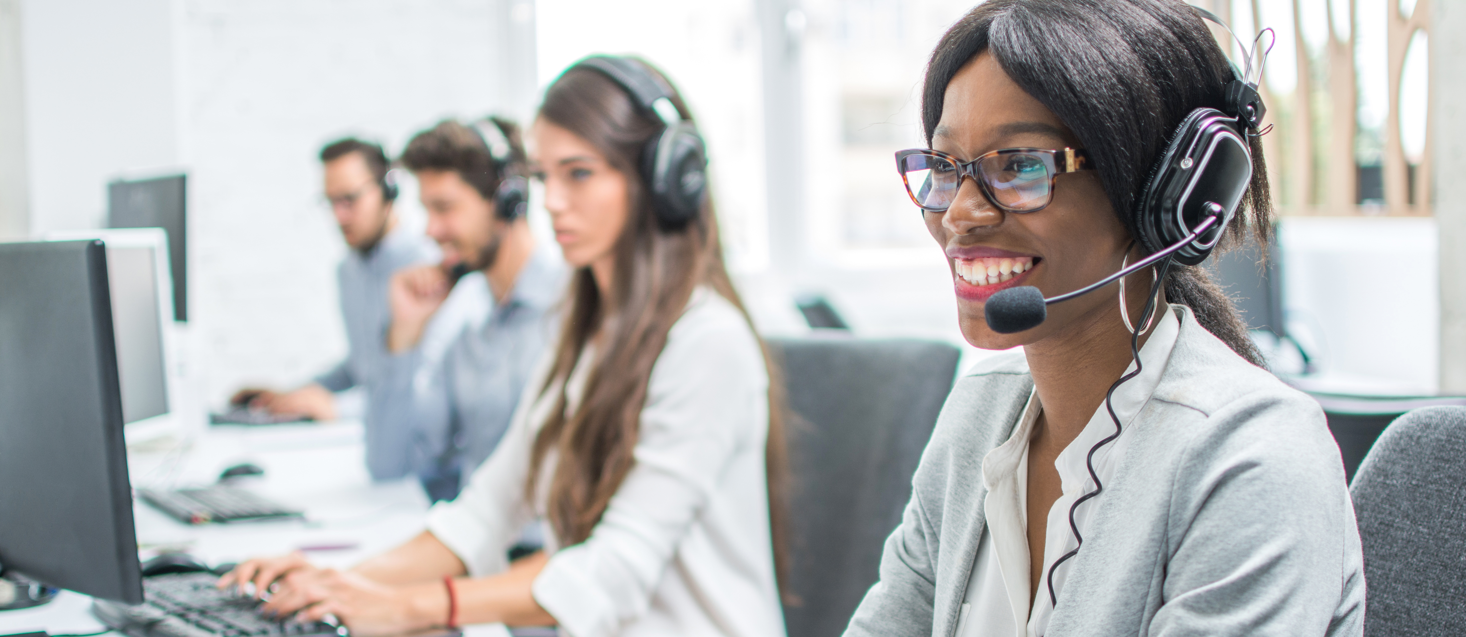 Smiling young woman with headset working in call center.